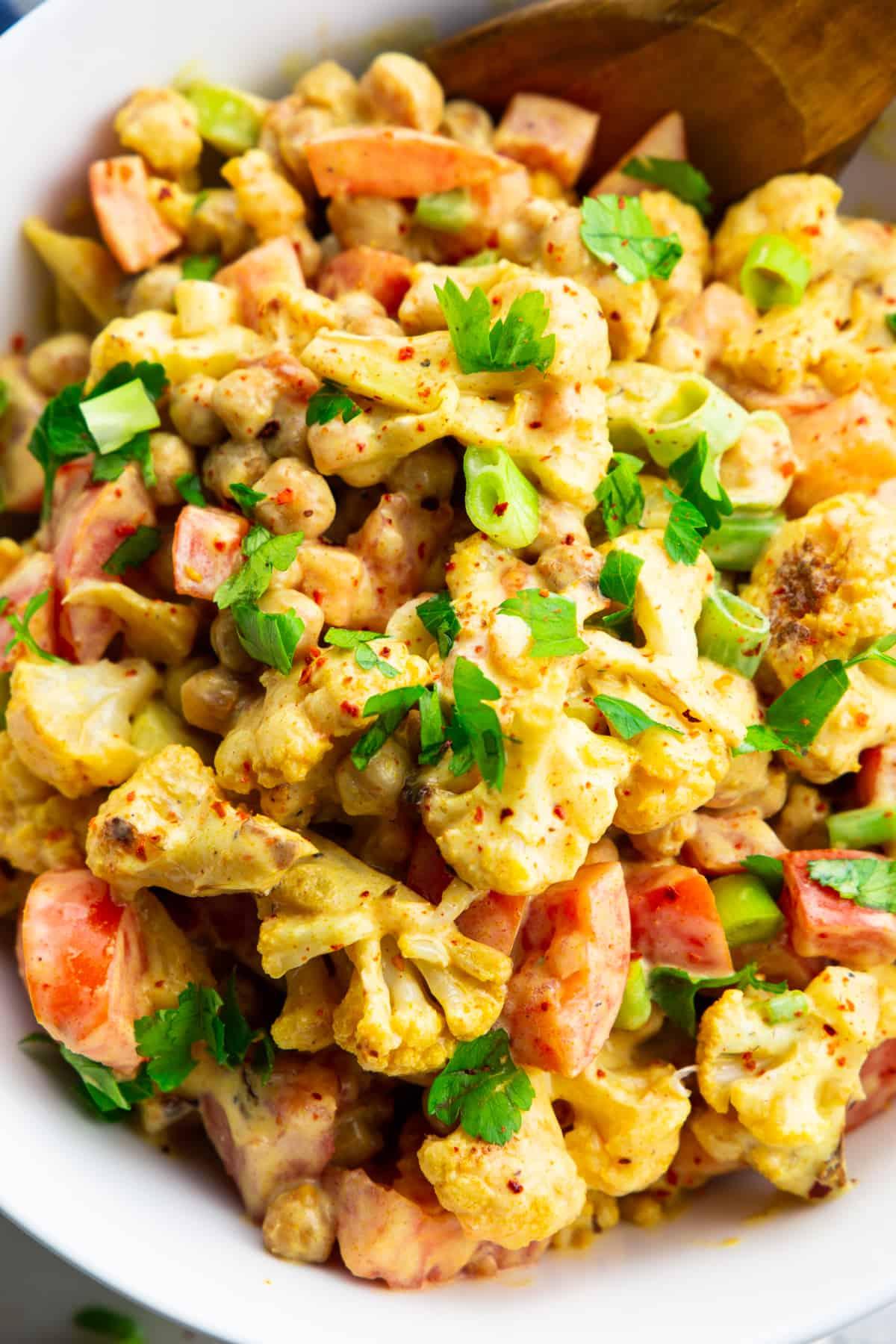 Nahaufnahme eines Salats mit Blumenkohl, Kichererbsen, Tomaten und Frühlingszwiebel in einer Schüssel