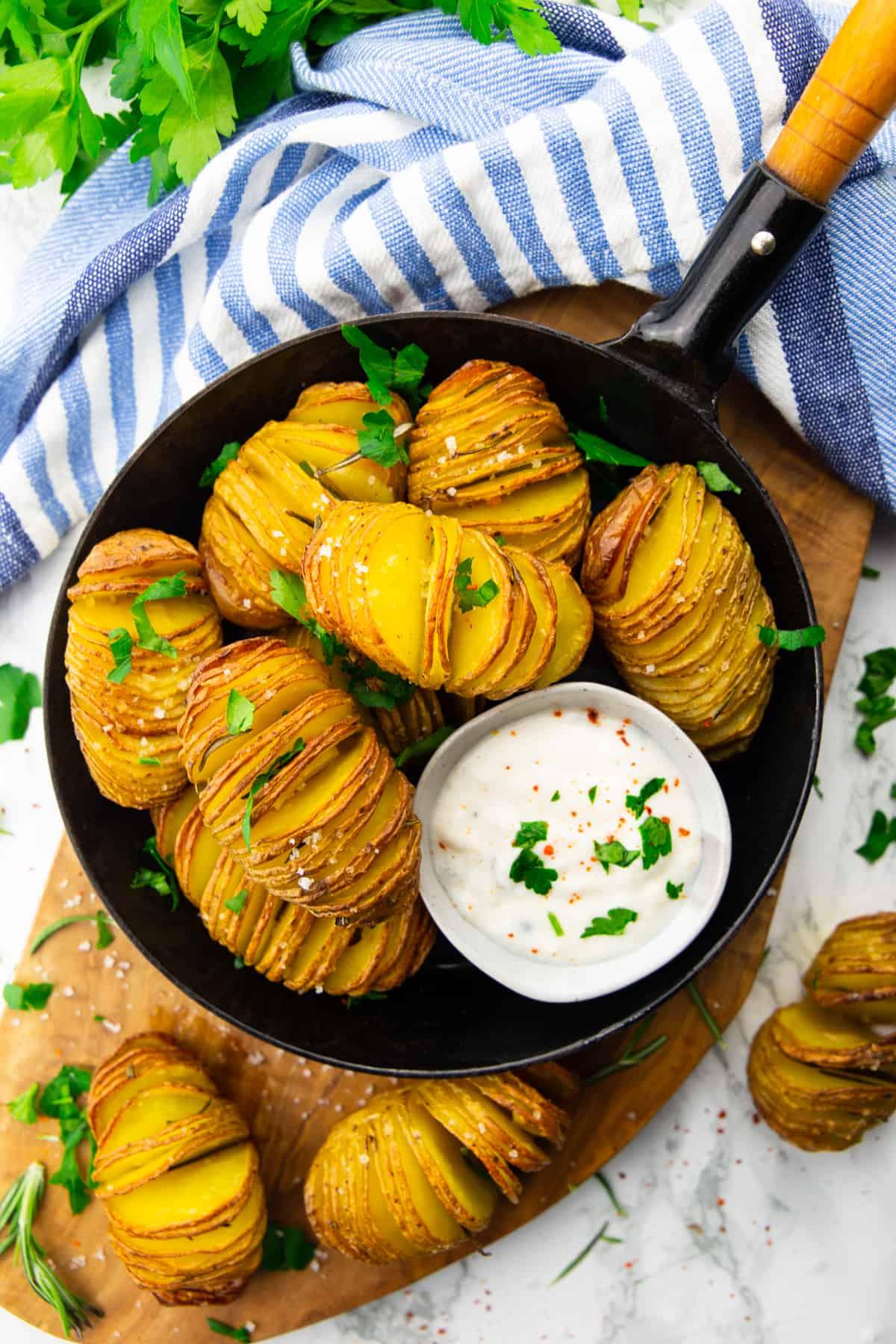 Fächerkartoffeln in einer Pfanne mit Sour Cream in einem kleinen Schälchen auf einer Holzplatte
