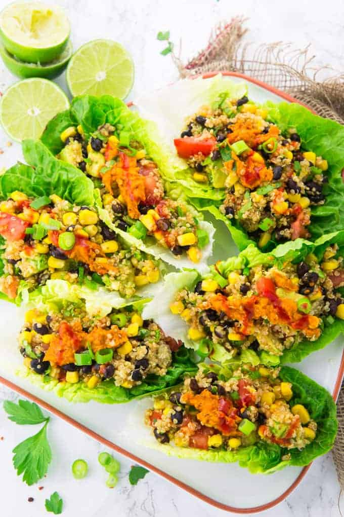 Salatwraps gefüllt mit Quinoa, Mais und Bohnen auf einem weißen Teller mit Limetten im Hintergrund