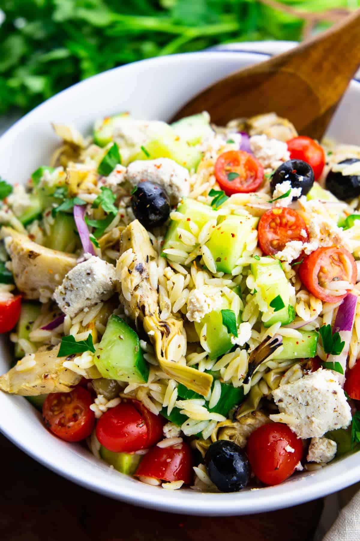 Risoni Salat in einer weißen Schüssel mit einem Holzlöffel mit Petersilie im Hintergrund
