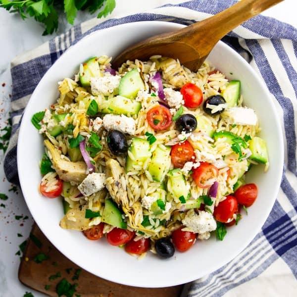 Risoni Salat in einer weißen Schüssel mit einem Holzlöffel auf einer Marmorplatte