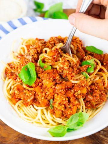 ein Teller mit Spaghetti Bolognese mit einer Hand, die eine Gabel hält