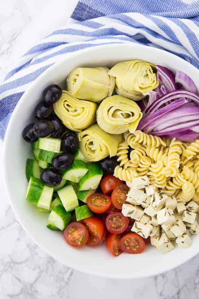 Veganer Feta mit Gurke, Tomate, Artischocken und Oliven in einer weißen Schüssel auf einer Marmorplatte