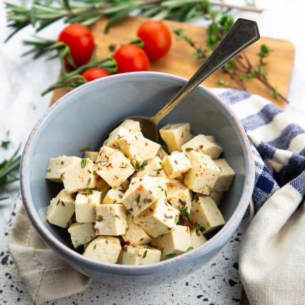 Veganer Feta in einer blauen Schale mit einem Löffel und Kirschtomaten und Kräutern im Hintergrund
