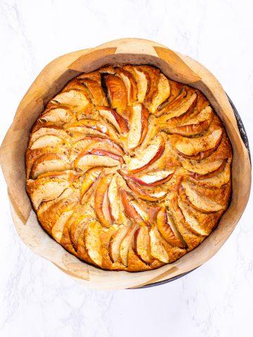 ein veganer Apfelkuchen in einer mit Backpapier ausgelegten Springform