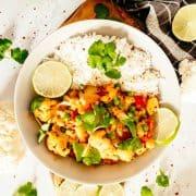 ein weißer Teller mit Blumenkohl Curry und Reis auf einer Marmorplatte mit Limetten im Hintergrund