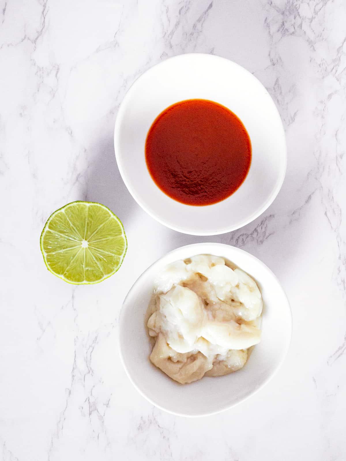 Zutaten für Sriracha Mayonnaise in Schüsseln auf einer Marmorplatte