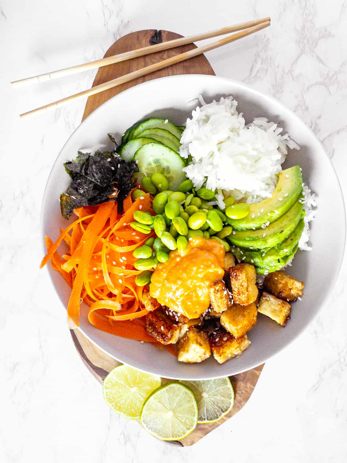 eine Sushi Bowl mit Tofu au einem Holzbrett mit Essstäbchen
