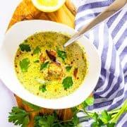 Brokkoli Suppe in einem weißen Teller mit einem Löffel auf einem Holzbrett