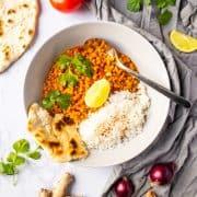 Linsen Dal mit Basmati Reis und Naan Brot in einem weißen Teller mit einem Löffel