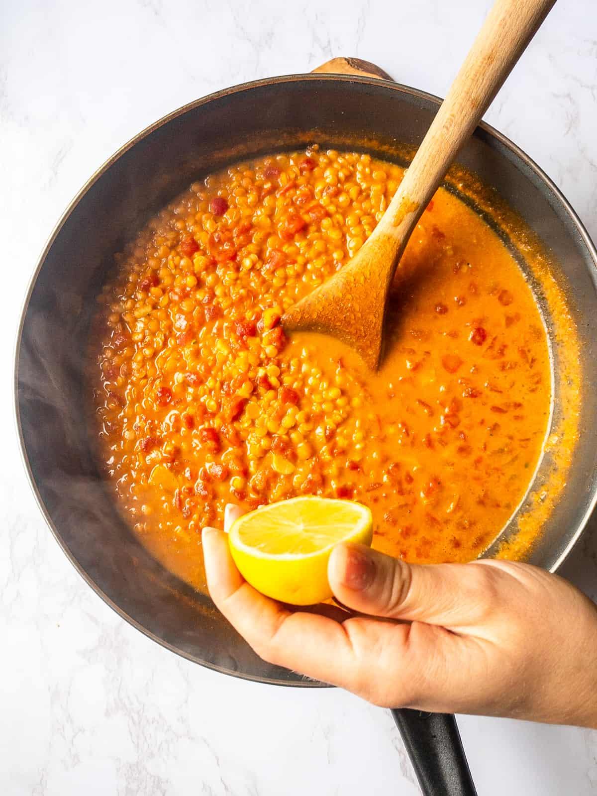eine Hand presst frischen Zitronensaft in eine Pfanne mit Dal