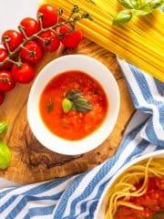eine weiße Schale mit Tomatensoße auf einem Holzbrett mit Spaghetti und Tomaten daneben
