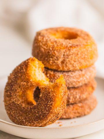 fünf vegane Donuts auf einem beigen Teller mit einem angebissenen Donut im Vordergrund