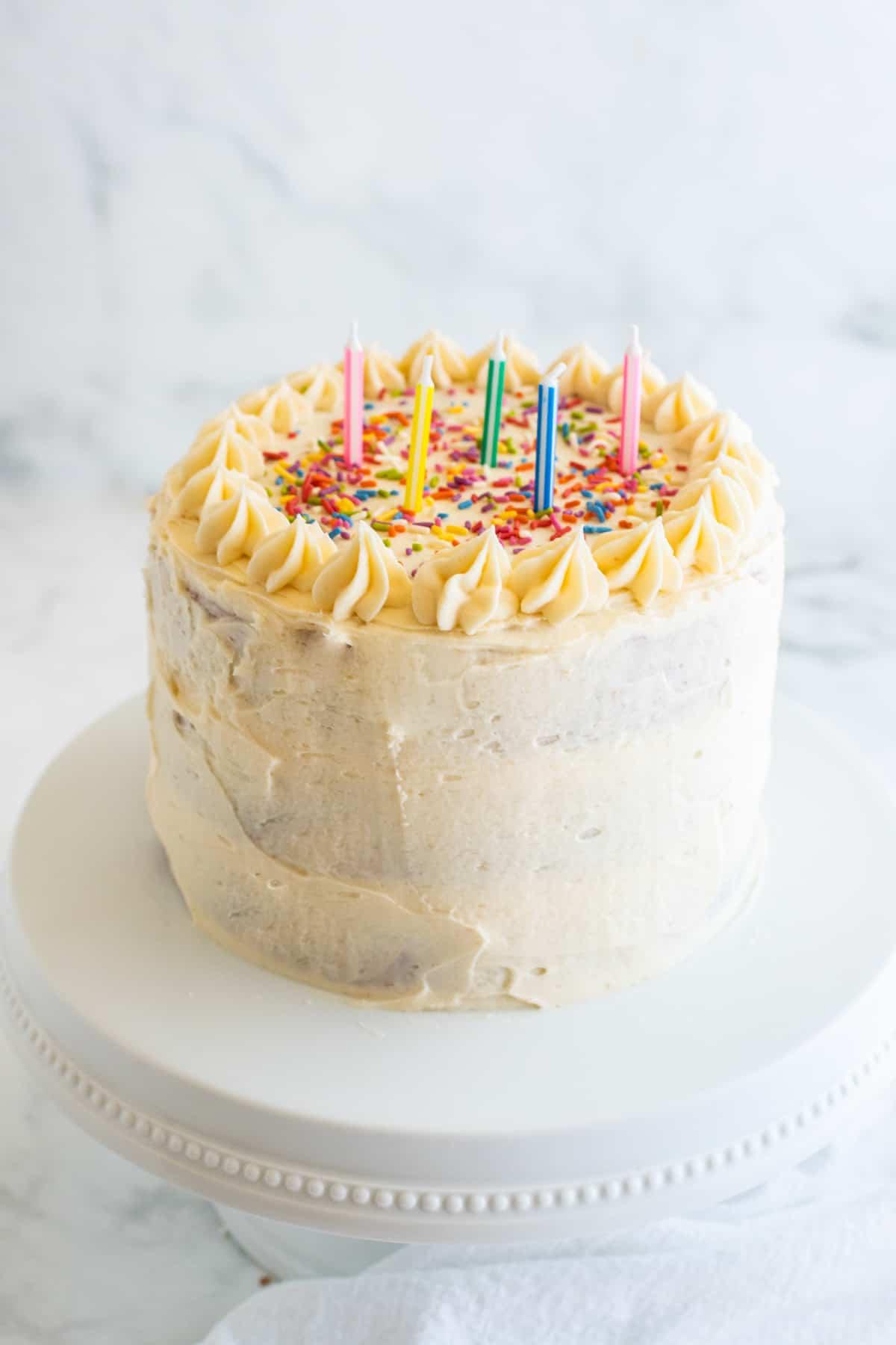 eine Torte mit Zucker Frosting und Streuseln auf einer weißen Kuchenplatte