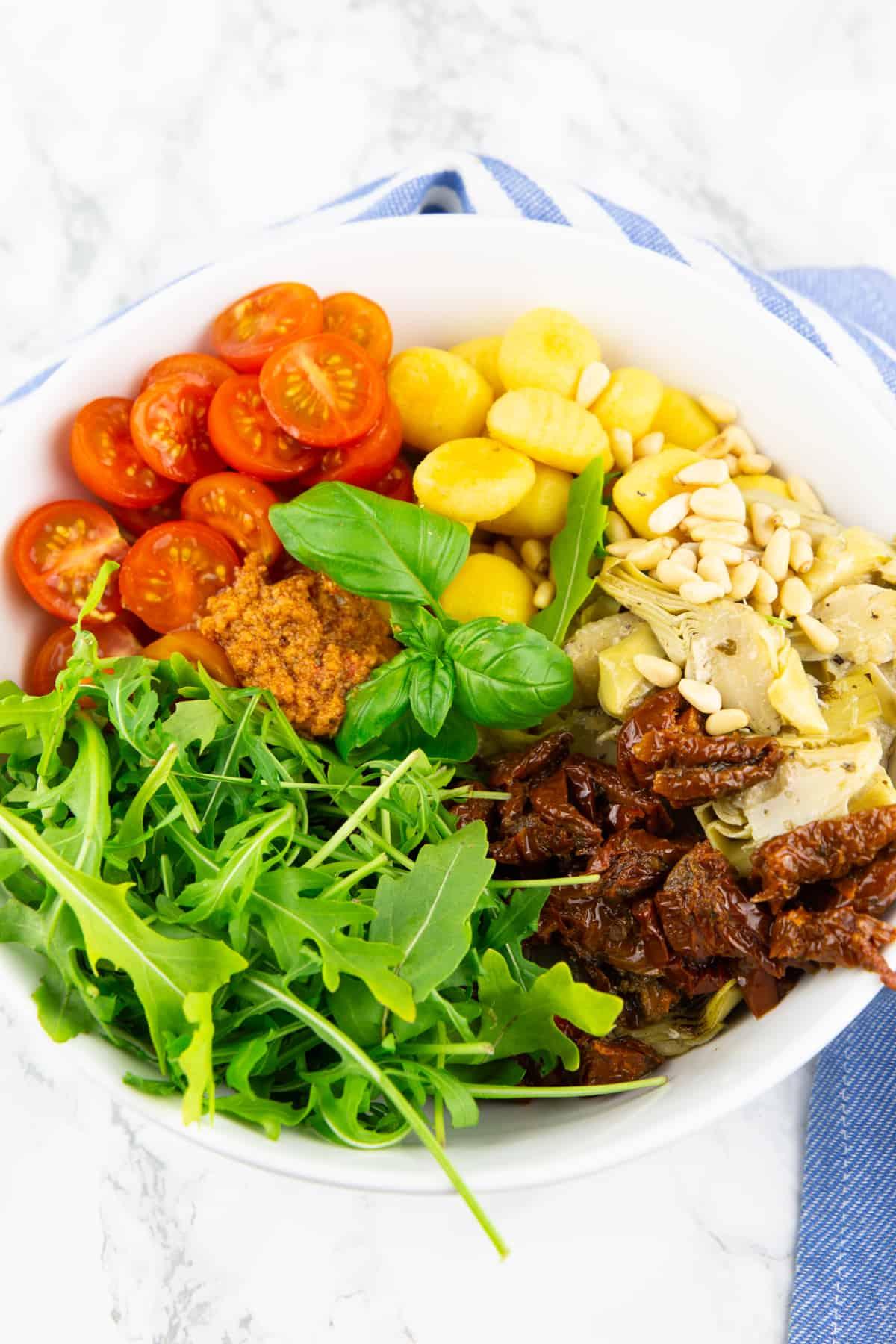 alle Zutaten für den Gnocchi Salat in einer weißen Schüssel auf einer Marmorplatte