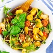 Gnocchi Salat mit Artischocken, getrockneten Tomaten und Rucola in einer weißen Schüssel mit einem Holzlöffel