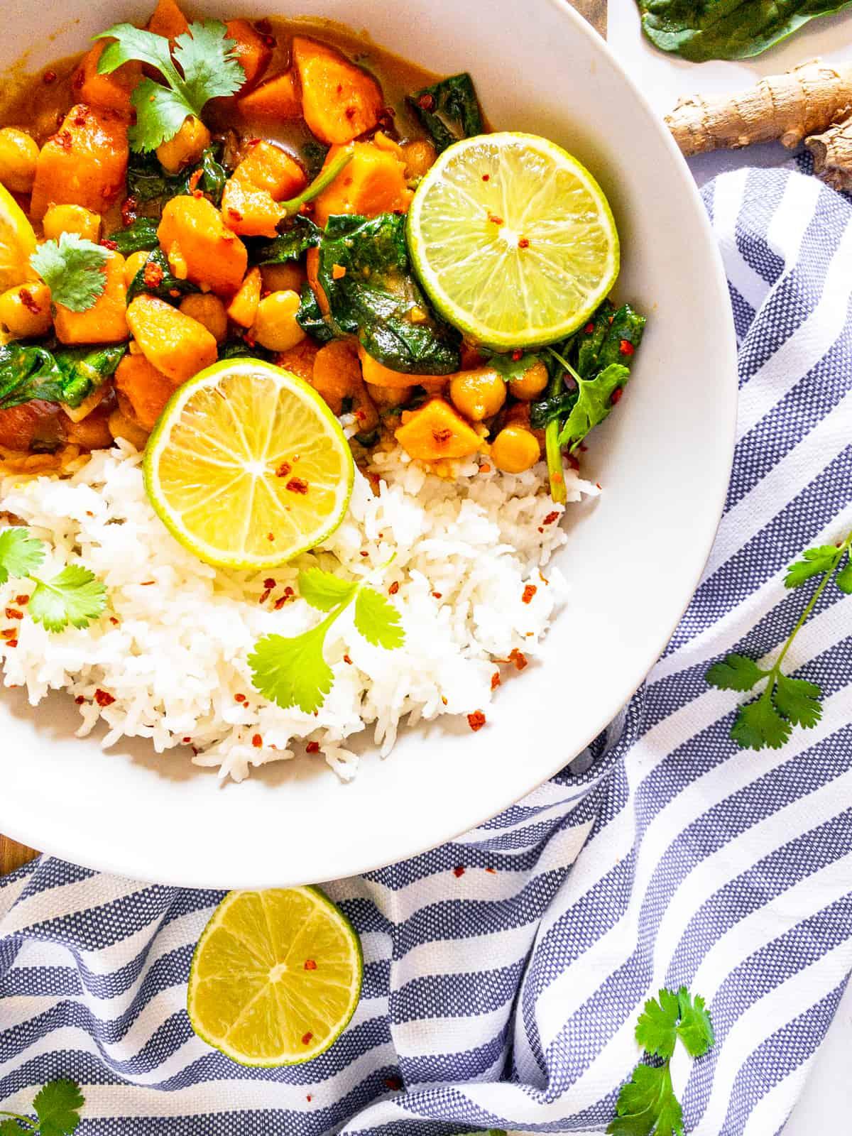 ein weißer Teller mit Reis und Süßkartoffelcurry auf einer blau weißen Tischdecke