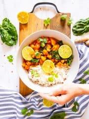 eine Hand, die einen Teller mit Süßkartoffel Curry hält