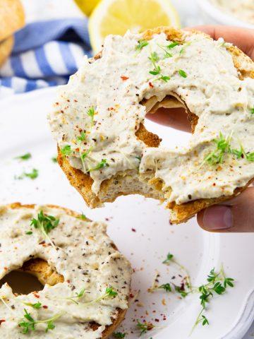 zwei Bagelhälften mit veganem Frischkäse bestreut mit frischen Kräutern